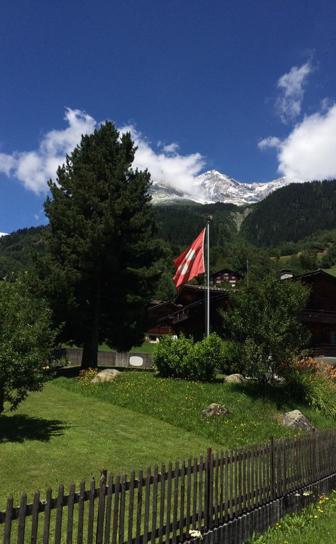 Schweizerfahne vor Schneebergen. Blauer Himmel mit Federwolken.